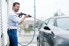 Carro de lavagem do homem na estação da lavagem de carros Fotografia de Stock Royalty Free
