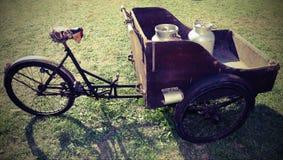 carro de madeira antigo com a bicicleta velha para transportar o leite j Fotos de Stock