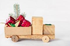 Carro de madeira do brinquedo velho do vintage com presentes e bolas do Natal Imagem de Stock