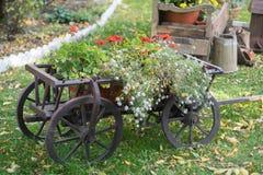 Carro de madeira do vintage com flores do verão fotos de stock
