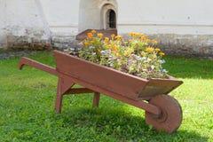 Carro de madera con las flores Foto de archivo libre de regalías