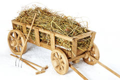 Carro de madera del heno en un fondo blanco Bifurcaciones y rastrillos Foto de archivo