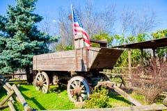 Carro de madera del oeste viejo con la bandera foto de archivo libre de regalías