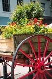 Carro de madera viejo con la rueda roja como plantador Imágenes de archivo libres de regalías