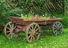 Carro de madera viejo con las flores Foto de archivo