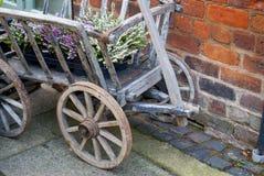 Carro de madera viejo de la rueda con las plantas del brezo en él Foto de archivo libre de regalías