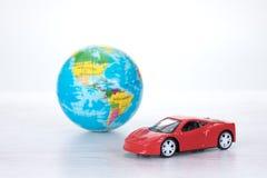 Carro de motor vermelho desportivo do brinquedo com um globo do mundo Fotos de Stock