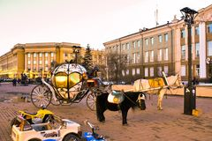 Carro de oro en la plaza de Irkutsk con un caballo blanco y de pie al lado del potro negro imagen de archivo