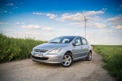 Carro de Peugeot em um campo com moinhos de vento imagem de stock