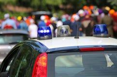 carro de polícia com as sirenes azuis na rua que acompanha participantes Fotos de Stock