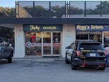 Carro de polícia ao lado de uma loja da filhós Fotografia de Stock Royalty Free