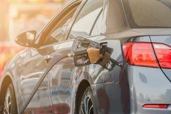 Carro de prata pequeno que reabastece no posto de gasolina Fotografia de Stock