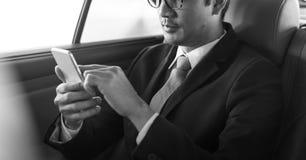 Carro de Use Mobile Inside do homem de negócios imagem de stock