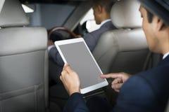 Carro de Use Tablet Inside do homem de negócios foto de stock