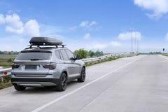 Carro de viagem de SUV com a caixa do telhado na estrada contra o céu azul Foto de Stock