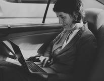 Carro de Working Using Laptop da mulher de negócios dentro do conceito imagem de stock