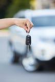 Carro defocused no fundo e na mão da mulher com chave Fotografia de Stock