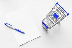 Carro del colmado y de la hoja de papel en blanco con la pluma en el fondo blanco Ideas del negocio de la lista de compras Imagen de archivo