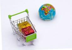 Carro del ultramarinos en nieve con Año Nuevo de las cajas de regalo en el fondo del globo Envío internacional de compras y de re Imagen de archivo