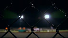 Carro detrás de una cerca que ve un equipo de fútbol de la High School secundaria metrajes