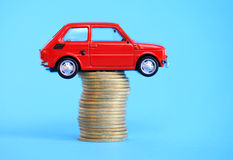 Carro diminuto vermelho na pilha da moeda Fotos de Stock Royalty Free