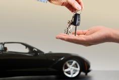 Carro do borrão na chave do carro da terra arrendada do fundo e da pessoa nas mãos foto de stock