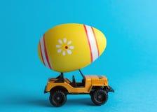 Carro do brinquedo com o ovo da páscoa colorido no fundo brilhante Conceito mínimo de easter foto de stock
