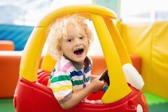 Carro do brinquedo da equitação da criança Rapaz pequeno com brinquedos imagens de stock