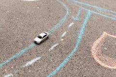 Carro do brinquedo em um asfalto marcações de estrada pintadas giz movimento à direita, rotação e tira fotos de stock royalty free