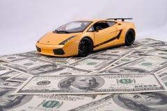 Carro do brinquedo no fundo do dinheiro Imagem de Stock Royalty Free