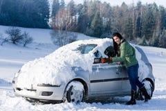 Carro do inverno - a mulher remove a neve do pára-brisa fotografia de stock royalty free