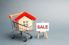 Carro do supermercado com casas e um cartaz da venda O conceito de vender uma casa, uns serviços dos bens imobiliários ou uma com imagens de stock royalty free