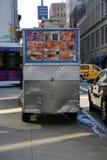 Carro do vendedor de New York City e táxi amarelo que passam perto foto de stock