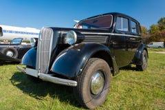 Carro do vintage que fica no por do sol Fotografia de Stock