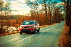 Carro e estrada asfaltada vermelhos Fotografia de Stock Royalty Free