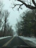 Carro e estradas nevado adiante Fotografia de Stock Royalty Free
