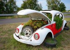 Carro e flores oxidados velhos imagens de stock royalty free