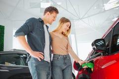Carro elétrico de compra de sorriso novo dos pares primeiro na sala de exposições Mulher que carrega o veículo eco-amigável moder imagens de stock royalty free