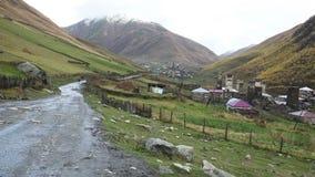 Carro em sua maneira no lugar turístico agradável Ushguli situado no pé de Shkhara, uma das cimeiras caucasianos as mais altas video estoque