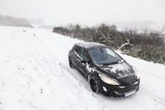 Carro em uma estrada coberto de neve Imagens de Stock Royalty Free