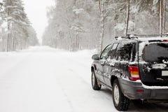 Carro em uma estrada de floresta nevado Fotos de Stock Royalty Free