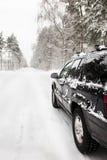 Carro em uma estrada de floresta nevado imagens de stock royalty free