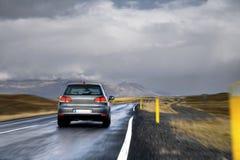 Carro em uma estrada em um campo Fotos de Stock