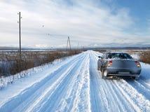 Carro em uma estrada nevado Imagens de Stock Royalty Free