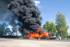 Carro en fuego con humo negro en el camino Imágenes de archivo libres de regalías