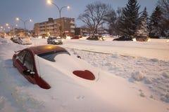 Carro enterrado na rua durante a tempestade da neve em Montreal Canadá imagem de stock