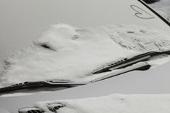 Carro estacionado coberto com a primeira neve no inverno Foto de Stock
