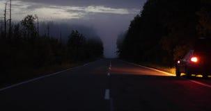 Carro estacionado na borda da estrada na noite com luzes de emergência sobre filme