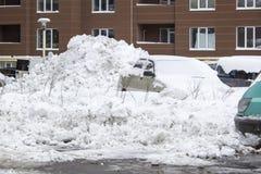 Carro estacionado sob a tampa de neve Fundo de estacionamento do inverno fotografia de stock