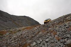 Carro fora de estrada grande de SUV na montanha rochoso fotos de stock royalty free